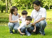 Happy Asian family having fun at outdoor park