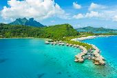 Travel vacation paradise aerial drone video with overwater bungalows luxury resort in coral reef lag poster