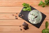 Mint And Choco Ice Cream Cup Decorated With Mint Leaves And Chocolate Chips On Slate Dish On A Woode poster