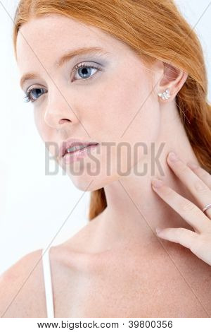 Closeup facial portrait of natural redhead beauty girl daydreaming.