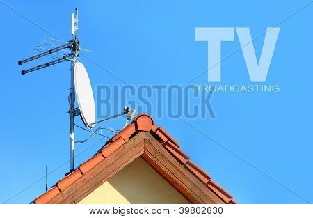 Red roof with a white satellite dish and WiFi antenna. Picture with space for your text.