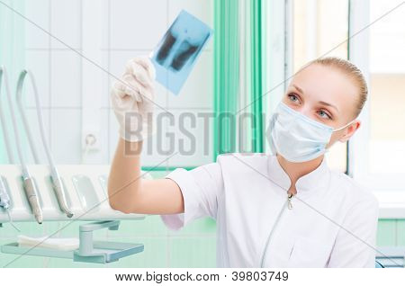 woman doctor in protective mask looking at x-ray