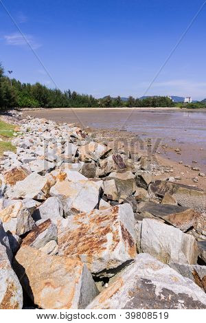 Rock for soil protection when low tide with blue sky background