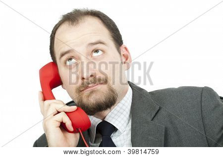 Businessman rolling his eyes as he listens to a boring phone call or message
