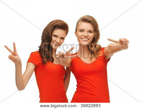 picture of two teenage girls in red t-shirts showing victory sign