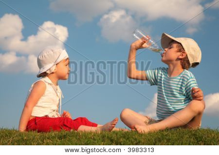 Boy And Girl Sit On Grass And Drink From Bottle