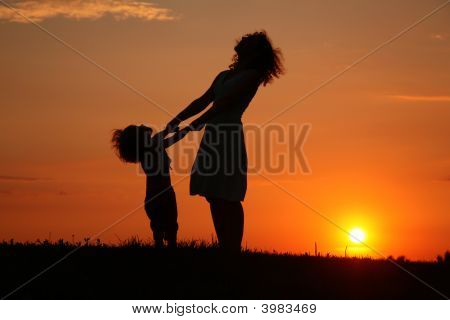 Mother And Daughter On Sunset Watching On Sky