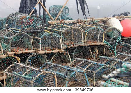 Lobster pots and creels in Scarborough harbor with fog background, England.