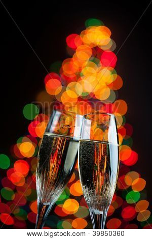 champagne glasses against christmas tree bokeh lights