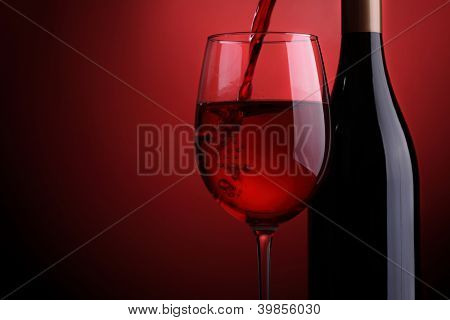 Red wine being poured into a glass with bottle against a red background