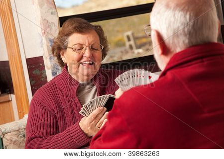Happy Senior Adult Couple Playing Cards in Their Travel Trailer RV.