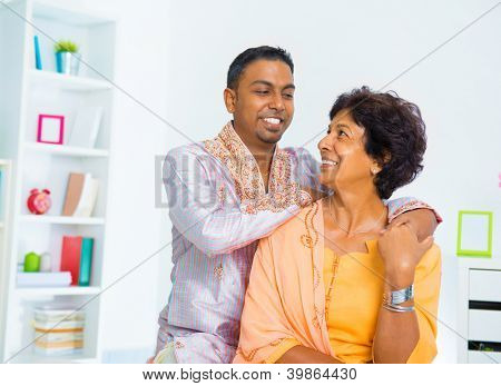 Asian Indian family, adult son having conversation with senior mother indoor.