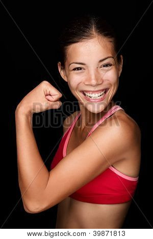 Playful young female Asian athlete flexing her arm with a mischievous smile to display her arm muscles. Fun upper body portrait on a black background