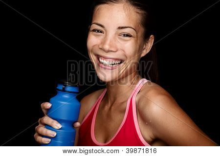 Smiling fitness sportswoman with a blue sport bottle on black background. Multiracial Asian fitness model happy.