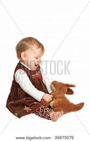 Cute Baby Looks Lovingly At Stuffed Toy