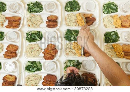 Multiple portions of fresh food being dished out onto individual serving trays
