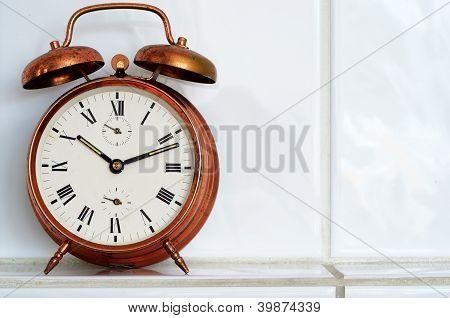 Vintage Copper Alarm Clock On The Mantelshelf