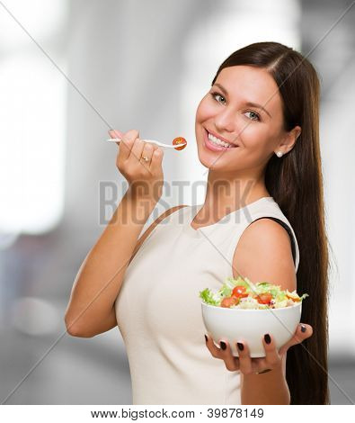 Portrait Of A Young Woman Holding A Salad against an abstract background