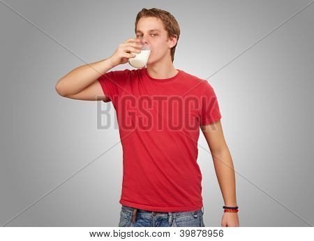 portrait of young man drinking milk over grey background