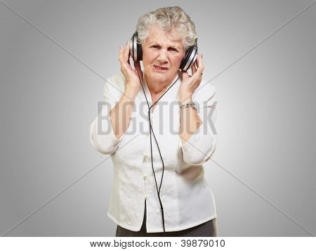 portrait of senior woman listening to music over grey background