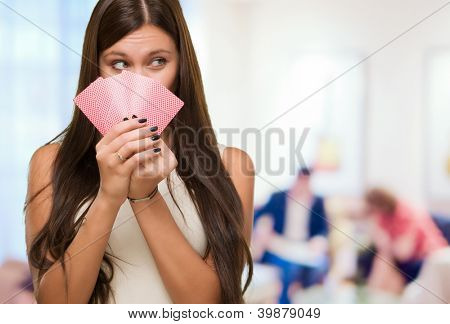 Pretty Young Woman Holding Playing Cards against an abstract background