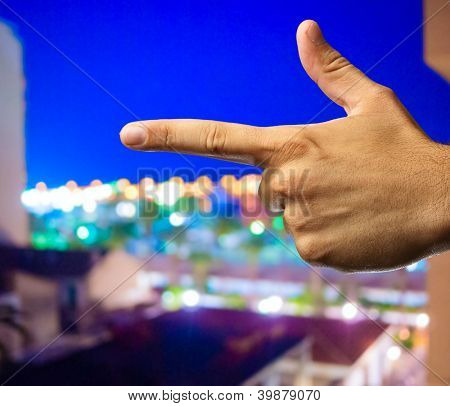 Human Hand pointing with finger isolated on a city by night background