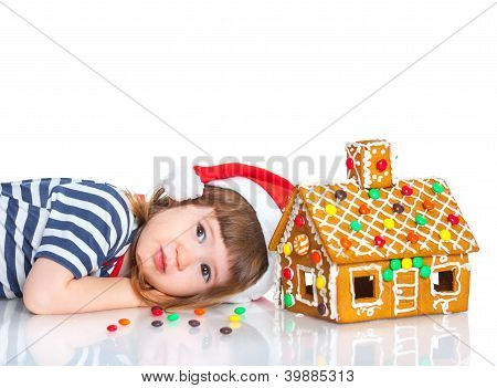 Little girl in Santa's hat with gingerbread house