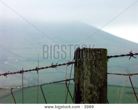 Barbed Wire Fence Against The Hill