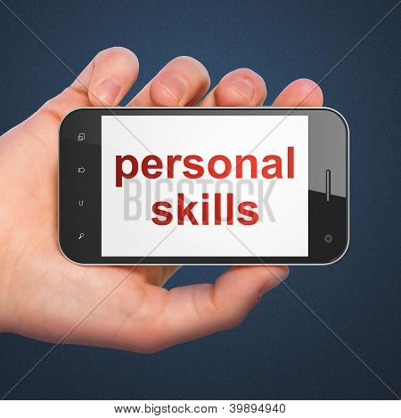 Hand holding smartphone with word personal skills on display. Ge