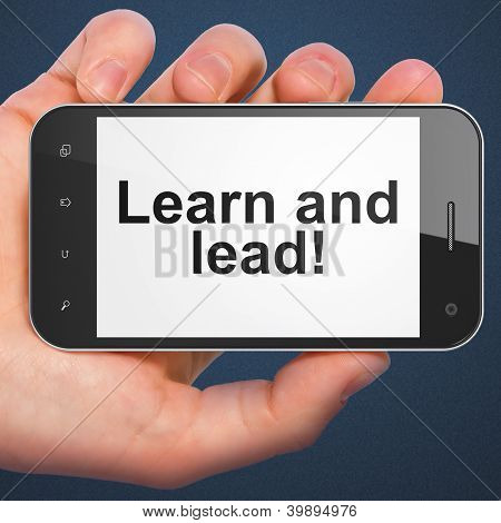 Hand holding smartphone with word Learn and lead! on display. Ge