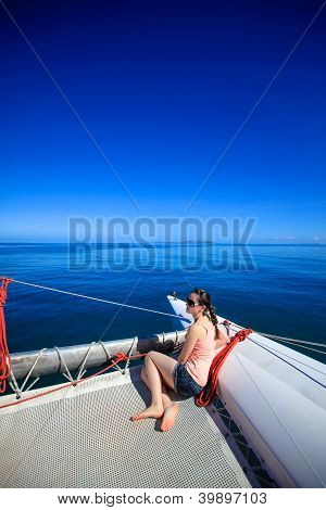 Young caucasian woman sitting in front of a boat
