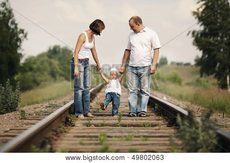 parents with baby on railroad