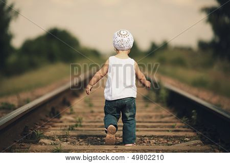 little girl plays on railroad