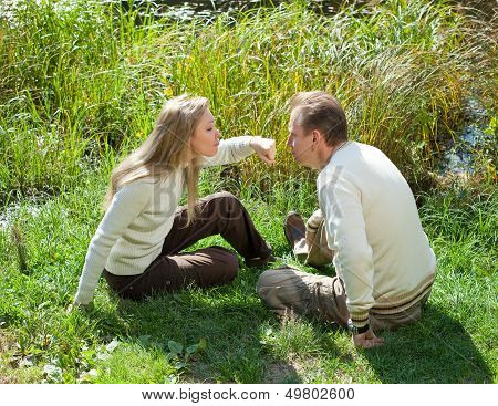 The beautiful woman for fun threatens to knock the man on a nose in the summer on a grass at the lak