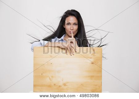 Beautiful woman with blank parole background ask for silence