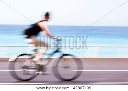Great way to get around in a city -Motion blurred cyclist going fast on a city bike lane, by the sea shore