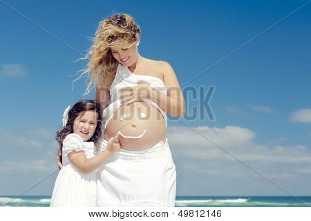 Beautiful pregnant woman in the beach with her little daugther making a smile on mom's belly with sunscreen