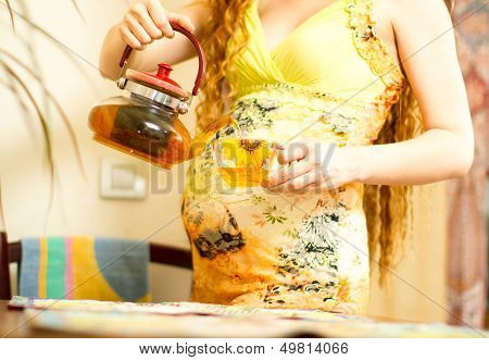 Pregnant Woman  With A Cap Of Tea On Kitchen. The Concept Of Drinking And A Healthy Lifestyle