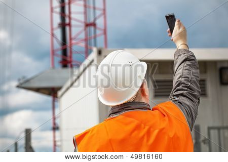 Engineer with the cell phone near to gsm tower