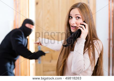 Security - disguised burglar breaking in an apartment or office, a woman calling the police with her phone or telephone