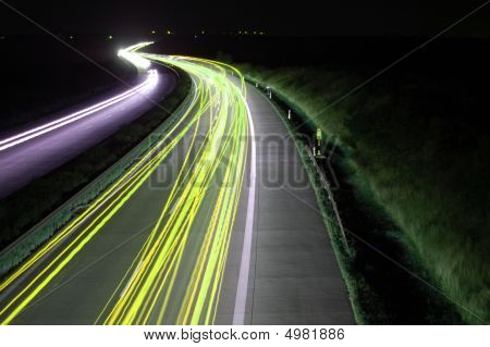 Road With Car Traffic At Night With Blurry Lights