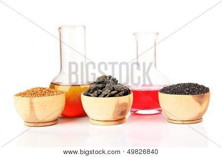 Beakers with bio fuel from rape seeds, oil cakes, isolated on white