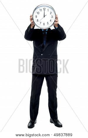 Executive Holding Up Wall Clock In Front Of His Face