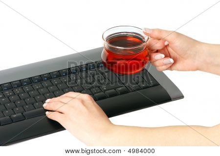 Woman's Hands Typing And Holding A Cup Of Tea