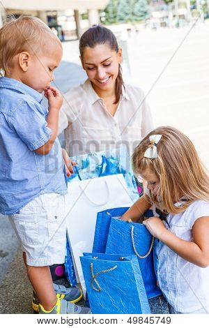 Kids looking into shopping bags beside the mall