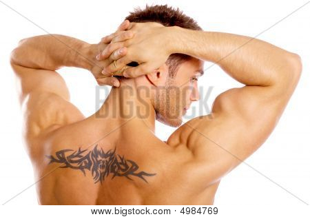 Muscular man with tattoo flexes his arms