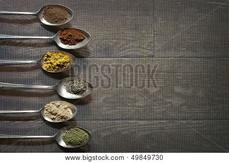 Six Antique Silver Spoons With Different Spices In Each Of Them