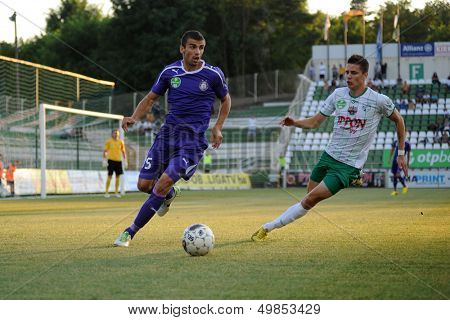 KAPOSVAR, HUNGARY - AUGUST 16: Benjamin Balazs (in white) in action at a Hungarian National Championship soccer game - Kaposvar (white) vs Ujpesti TE (purple) on August 16, 2013 in Kaposvar, Hungary.