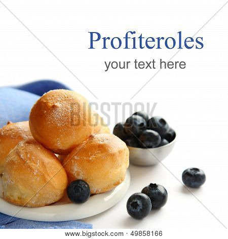 Profiteroles And Blueberries Over White With Sample Text
