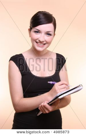 Young Woman Holding Notepad And Pen